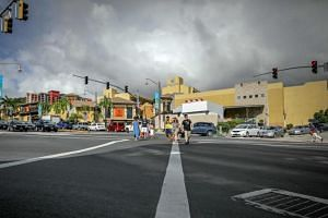 People walk across an intersection in the city of Tamuning on the island of Guam on August 10, 2017.