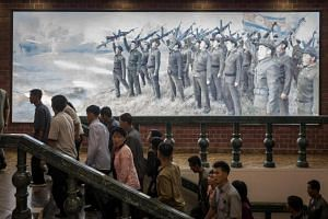 People walk up stairs before a propaganda poster showing Korean People's Army soldiers at a museum in Sinchon, south of Pyongyang.
