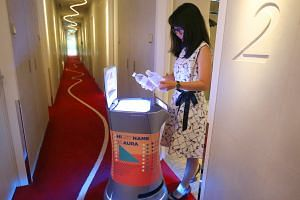 Aura the robot delivering bottled water to a hotel room at M Social Singapore. The robot is able to find its own way around the hotel to deliver room amenities to guests. At the hotel, one robot can do the work of two to three people, and takes an av