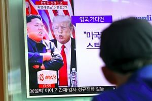 A man watches a television news programme showing US President Donald Trump (centre) and North Korean leader Kim Jong-Un at a railway station in Seoul on Aug 9, 2017.