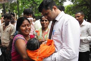 A woman with a child in her arms at the Baba Raghav Das Hospital in Gorakhpur, Uttar Pradesh, last Friday. All the deaths had occurred at the hospital's paediatric ward over a five-day period starting last Monday, said a statement from the chief mini