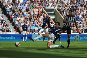 Tottenham Hotspur's midfielder Dele Alli scores his team's first and the opening goal during the English Premier League football match between Newcastle United at St James' Park in Newcastle-upon-Tyne, north east England on August 13, 2017.