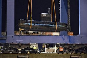 Submarine UC3 Nautilus is lifted onto a block truck from the salvage ship Vina with the help of a container crane in Copenhagen's Harbor, Denmark on August 12, 2013.