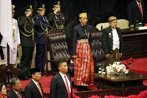 Indonesian President Joko Widodo (centre), accompanied by his Vice-President Jusuf Kalla (right), sings the national anthem in Jakarta, Indonesia, on Aug 16, 2017.