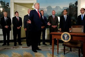 US President Donald Trump responds to a reporter's question after signing a memorandum directing the US Trade Representative to complete a review of trade issues with China, on Aug 14, 2017.