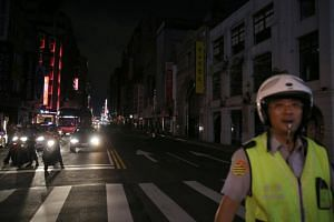 A police stands in front of a building during a massive power outage in Taipei, Taiwan, on Aug 15, 2017.
