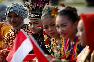 Students in traditional costume waiting for Independence Day celebrations to start at the National Monument in Jakarta yesterday. All three of Mr Joko Widodo's speeches on Wednesday were dominated by the theme of unity.
