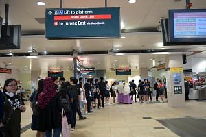 Commuters, who are mostly students, queueing to get a time chit from SMRT at Bishan MRT station on Aug 18, 2017.