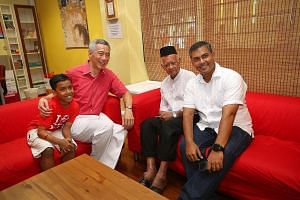 "Prime Minister Lee Hsien Loong with (from left) nine-year-old Adam Zafran Aziz, Mr Ahmad Azali, 79, and Mr Aziz Ahmad, 42. Mr Lee said: ""This is the Singapore of the last half century: Ahmad, a gardener; Aziz, a pharmaceu- tical engineer; and Adam, ("