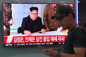 A television news screen showing North Korean leader Kim Jong Un at a railway station in Seoul on Aug 15, 2017.