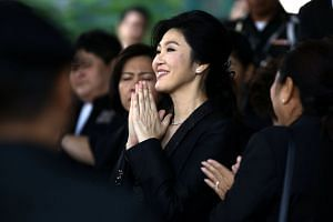 Ousted former Thai prime minister Yingluck Shinawatra greets supporters as she leaves the Supreme Court in Bangkok.
