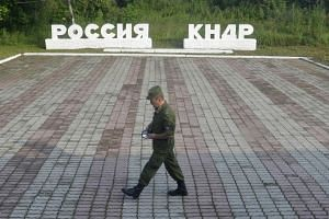 "A guard walks past signs reading ""Russia"" (left) and ""DPRK"", in Tumangan, North Korea."