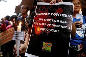 Protesters hold placards and lighted candles at the wake of Kian Loyd delos Santos who was among the people shot dead last week in an escalation of President Rodrigo Duterte's war on drugs in Caloocan city, Metro Manila, Philippines on Aug 21, 2017.