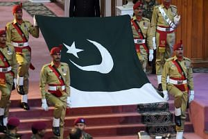 Pakistani soldiers carry national flag during a ceremony to mark the country's Independence Day in Islamabad on Aug 14, 2017.