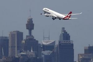 A Qantas Airways jet takes off from Sydney International Airport.