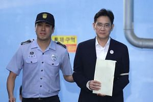 Lee Jae Yong, vice-chairman of Samsung Electronics, is escorted by a prison officer as he leaves the Seoul Central District Court in Seoul, South Korea, on Friday (Aug 25). ,