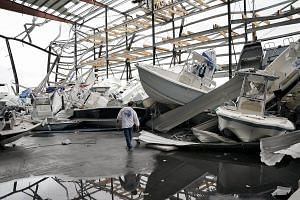 Dominic Dominguez searches for his boat in a boat storage facility that was heavily damaged by Hurricane Harvey near Rockport, Texas.