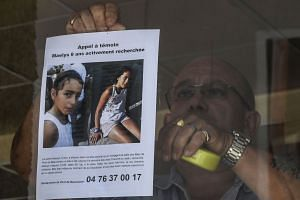 The owner of a bar attaches a missing poster issued by police for nine-year-old Maelys.