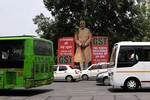 Indian motorists drive past a billboard displaying an image of Prime Minister Narendra Modi and announcing the implementation of the Goods & Service Tax (GST) in New Delhi, on July 4, 2017.