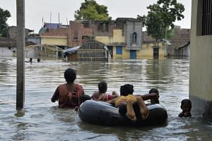 Indian residents wade through flood waters in Malda in the Indian state of West Bengal.