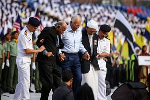 Malaysia Prime Minister Najib Razak (centre) with retired army officers Oliver Culvelt Samuel (second, left) and Mohamed Sharif Kalam (second, right), both of whom raised the national flag on the eve of Aug 31, 1957, at the full dress rehearsal for t