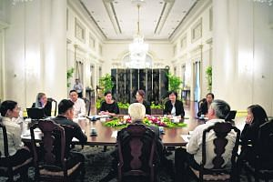 Above: President Tony Tan (back to camera) at a staff meeting with aides-de-camp and members of his staff (clockwise from his left) - Superintendent Dennis Lim, Major Valerie Chia, Ms Joanne Yan, ME6 Wong Kah Mun, Ms Seraphim Cheong, Ms Lai Choon Yen