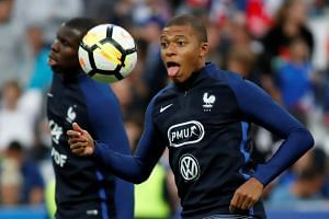 France's Kylian Mbappe warms up before a match.