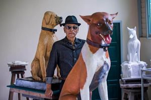Thai sculptor Chin Prasong poses for a portrait next to two sculptures of dogs owned by the late Thai King on Aug 31, 2017.