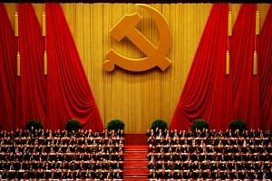 A general view shows delegates raising their hands as they take a vote at the closing session of the 18th National Congress of the Communist Party of China at the Great Hall of the People in Beijing on Nov 14, 2012.