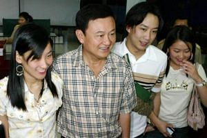 Thai Prime Minister Thaksin Shinawatra (second left) along with his children, (from left) elder daughter Pintongta, son Pantongtae and youngest daughter Paetongtan, after casting votes in downtown Bangkok on Feb 6, 2005.
