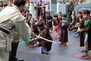 Vihaan Chopra (centre), 7, and younger brother Vinayak Chopra (centre right, blue t-shirt), 4, take part in a 30-min Padawan training, on Sept 1, 2017, the first day of 10-day Star Wars festival outside Ion Orchard shopping mall.