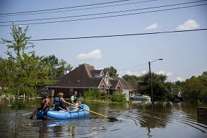 People riding into a flooded neighbourhood in Beaumont, Texas, on Sept 1, 2017.