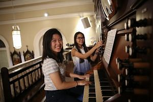 """Ms Nadine Wong (left) and Ms Anne Maria Lim, two of six candidates in the Cathedral Organ Scholar Programme, at the organ of the Cathedral of the Good Shepherd. Scholars """"graduate"""" when they can play at mass without assistance."""