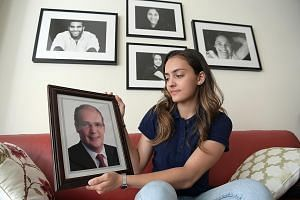 Amita Berthier, 16, won one of Singapore's two fencing gold medals at the SEA Games, a year after her dad Eric died. Amita holds a portrait of her father, who supported her in ways small and big. He was, among other things, her chief cheerleader, cha