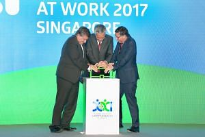 Prime Minister Lee Hsien Loong, ILO director- general Guy Ryder (far left) and ISSA president Joachim Breuer pushing a frame in the shape of a briefcase to launch the 21st World Congress on Safety and Health at Work yesterday.
