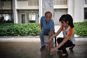 Retiree Loy See Wee, 68, doing the modified sit and reach test.