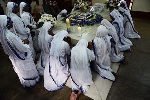 Roman Catholic nuns of the Missionaries of Charity praying at the tomb of Mother Teresa at a service to commemorate the 20th anniversary of her death at the order's house in Kolkata, India, yesterday. Pope Francis on Monday proclaimed Mother Teresa a