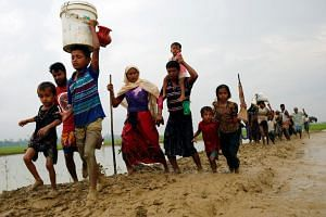 Rohingya refugees walk on the muddy path after crossing the Bangladesh-Myanmar border in Teknaf, Bangladesh, on Sept 3, 2017.