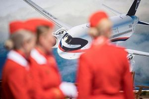Air hostesses from Russian airlines  stand in front of an advertising board depicting the new RusSian Sukhoi Superjet 100 airliner at an airshow outside of Moscow on July 18, 2017.
