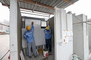 Workers adding finishings, such as tiles and window frames, to a pre-fabricated bathroom at a site in Bukit Batok.