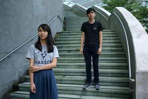 Hong Kong democracy activists Agnes Chow and Lester Shum pose for photos outside the Hong Kong government headquarters on Aug 29, 2017.