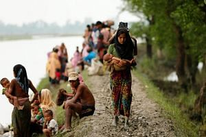 A Rohingya refugee woman with her child walks on the muddy path after crossing the Bangladesh-Myanmar border in Teknaf, Bangladesh on September 7, 2017.