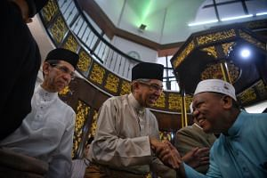 Minister-in-charge of Muslim Affairs Yaacob Ibrahim greeting a congregant after prayers at Al-Mukminin Mosque on June 25, 2017.