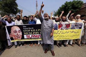 People holding a banner with picture of Myanmar democracy leader Aung San Suu Kyi, during a protest against violence in Myanmar, in Peshawar, Pakistan, on Sept 7, 2017.