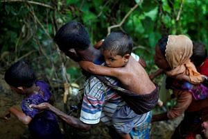 Rohingya refugees climb up a hill after crossing the Bangladesh-Myanmar border, Sept 8, 2017.