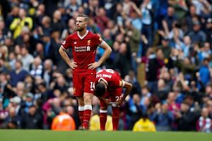 Liverpool's Jordan Henderson and Emre Can look dejected after Manchester City's Leroy Sane scores their fourth goal.