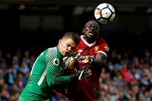 Manchester City's Ederson Moraes is fouled by Liverpool's Sadio Mane resulting in a red card for Mane.
