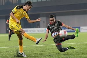 Brunei DPMM's Najib Tarif attempts to block a shot by Tampines' Ryutaro Megumi during their S-League match in July. Uncertainty surrounds the competition as a funding cut may force the league to shut down.