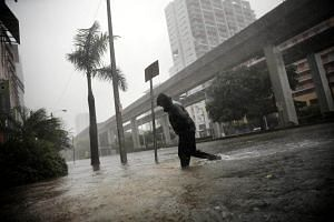 A local resident wades through a flooded street in downtown Miami, on Sept 10, 2017.