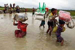 A Rohingya refugee woman falls as she walks through the water after crossing the border, in Teknaf, Bangladesh on Sept 1, 2017.